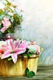 Букет и розы цветка лилии украшенные расположением в форме деревянного ведра вертикальной используют как домой тема флоры природы  Стоковые Изображения