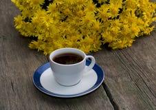 Букет красивых желтых цветков и чашки черного кофе Стоковые Фотографии RF