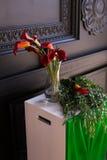 Букет красных лилий calla в стеклянной вазе с гранатовым деревом и евкалиптом Стоковые Изображения
