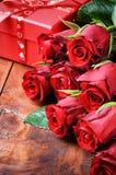 Букет красных роз и коробки подарка Стоковые Изображения