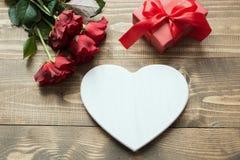 Букет красных роз и подарка с красной лентой и сердца на деревянной доске Валентайн карточки s скопируйте космос Стоковое Изображение RF