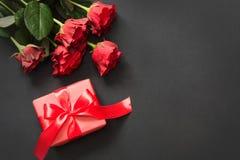 Букет красных роз и подарка с красным цветом на черной предпосылке Валентайн карточки s конец вверх скопируйте космос Стоковая Фотография RF