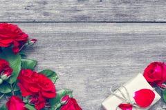 Букет красных роз и подарочной коробки на деревенской деревянной предпосылке Стоковое фото RF