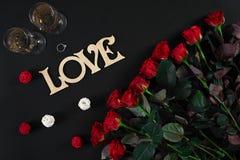 Букет красных роз и 2 стекел шампанского на черном bac Стоковые Изображения