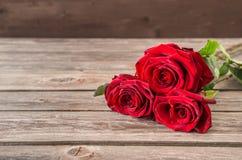 Букет красных роз на деревянной предпосылке Стоковые Фотографии RF
