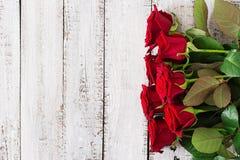 Букет красных роз на светлой деревянной предпосылке Стоковое Фото