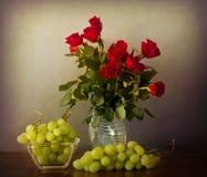Букет красных роз на стеклянной вазе и виноградинах дальше стоковые изображения rf