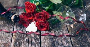 Букет красных роз, 2 стекел, бутылки вина, подарочной коробки с биркой на винтажной деревянной доске красный цвет поднял Стоковые Фото