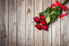 Букет красных роз с смычком на деревянной предпосылке красный цвет поднял Стоковая Фотография RF