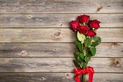 Букет красных роз с смычком на деревянной предпосылке красный цвет поднял Стоковые Фотографии RF
