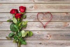 Букет красных роз с смычком на деревянной предпосылке красный цвет поднял Стоковое Фото