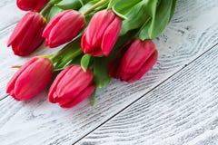 Букет красных тюльпанов на белом деревянном столе Стоковое Фото