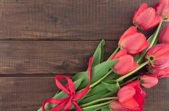Букет красных тюльпанов на деревянной предпосылке с космосом для текста Стоковая Фотография RF