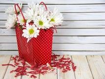 Букет маргаритки в красной сумке подарка точки польки стоковые фото