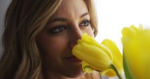 Букет молодой женщины усмехаясь и пахнуть цветков Стоковое Фото