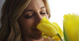 Букет молодой женщины усмехаясь и пахнуть цветков Стоковые Фото