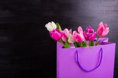 Букет нежных розовых тюльпанов в фиолетовой хозяйственной сумке на черном wo Стоковые Фотографии RF