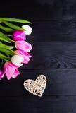 Букет нежных розовых тюльпанов и плетеного сердца на черном деревянном b Стоковые Изображения