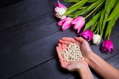 Букет нежных розовых тюльпанов и рук держа ожерелье o жемчуга Стоковая Фотография