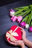 Букет нежных розовых тюльпанов и рук держа подарочную коробку на blac Стоковые Фотографии RF