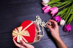 Букет нежных розовых тюльпанов и рук держа подарочную коробку на blac Стоковое фото RF