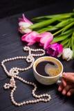Букет нежных розовых тюльпанов и рук держа чашку кофе Стоковые Изображения RF