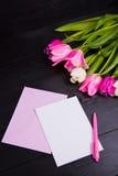Букет нежных розовых тюльпанов и ясной бумаги на черном деревянном ба Стоковое Фото