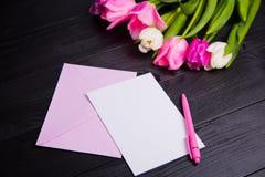 Букет нежных розовых тюльпанов и ясной бумаги на черном деревянном ба Стоковая Фотография