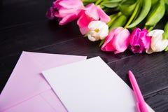 Букет нежных розовых тюльпанов и ясной бумаги на черном деревянном ба Стоковые Изображения RF