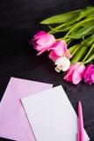 Букет нежных розовых тюльпанов и ясной бумаги на черном деревянном ба Стоковое Изображение