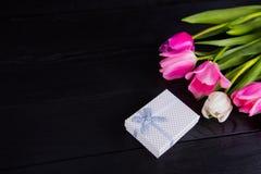 Букет нежных розовых тюльпанов с подарочной коробкой на черной деревянной задней части Стоковое Фото