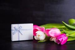 Букет нежных розовых тюльпанов с подарочной коробкой на черной деревянной задней части Стоковое Изображение