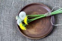 Букет одуванчиков связанных со шпагатом на круглом блюде коричневого цвета глины Грубый homespun холст, мешковина джута стоковые фото