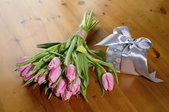 Букет пинка тюльпанов на красивых деревянных предпосылке и подарке Стоковое фото RF