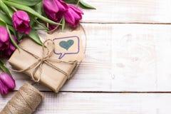 Букет подарочной коробки и тюльпанов на белой деревянной предпосылке Стоковая Фотография