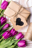 Букет подарочной коробки и тюльпанов на белой деревянной предпосылке Стоковое Изображение
