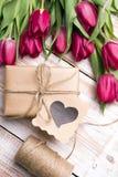 Букет подарочной коробки и тюльпанов на белой деревянной предпосылке Стоковые Изображения RF