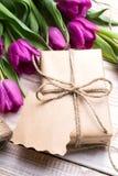 Букет подарочной коробки и тюльпанов на белой деревянной предпосылке Стоковое Фото