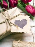 Букет подарочной коробки и тюльпанов на белой деревянной предпосылке Стоковые Фотографии RF