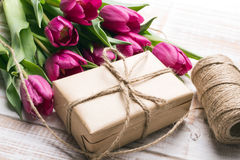 Букет подарочной коробки и тюльпанов на белой деревянной предпосылке Стоковая Фотография RF