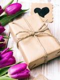 Букет подарочной коробки и тюльпанов на белой деревянной предпосылке Стоковое Изображение RF