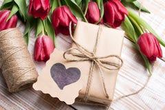 Букет подарочной коробки и тюльпанов на белой деревянной предпосылке - Стоковое Изображение RF
