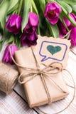 Букет подарочной коробки и тюльпанов на белой деревянной предпосылке - Стоковые Изображения RF