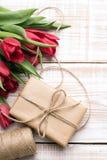 Букет подарочной коробки и тюльпанов на белой деревянной предпосылке Стоковое фото RF