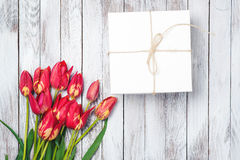 Букет подарочной коробки и тюльпанов на затрапезной белой деревянной предпосылке Космос для текста Взгляд сверху Стоковое фото RF
