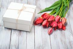 Букет подарочной коробки и тюльпанов на затрапезной белой деревянной предпосылке Космос для текста Селективный фокус Стоковая Фотография RF