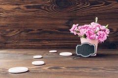 Букет розовой гвоздики цветет в вазе на деревянной предпосылке Пустой космос для текста Стоковое Фото