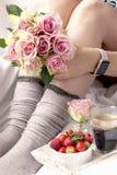 Букет розовых роз в руках девушки на кровати, ягод клубник и душистого кофе утра романско Стоковое фото RF