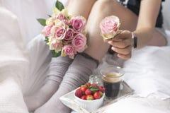 Букет розовых роз в руках девушки на кровати, ягод клубник и душистого кофе утра романско Стоковая Фотография RF