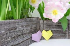 Букет розовых тюльпанов в деревянной коробке и 2 бумажных сердцах желтого цвета и цвета сирени на белой предпосылке стоковая фотография
